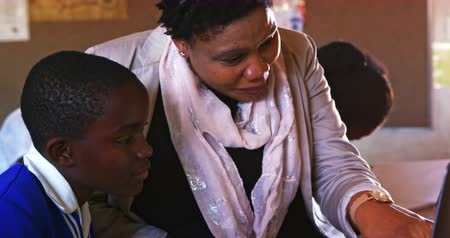 clase media : Front view close up of a middle aged African female school teacher helping a young African schoolboy sitting at his desk using a laptop computer during a lesson in a township elementary school classroom, while in the background classmates are busy working