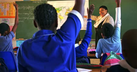 cape town : Rear view of a young African schoolchildren raising their hands to answer a question to the female teacher standing at the front of the class by the blackboard pointing at a map during a lesson in a township elementary school classroom 4k