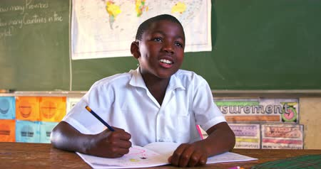 školák : Front view close up of a young African schoolboy sitting at a desk looking up while writing in his note book and listening attentively during a lesson in a township elementary school classroom 4k
