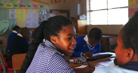 одноклассник : Side view close up of two young young African schoolgirls sitting at their desk talking to each other during a lesson in a township elementary school classroom. In the background their classmates are working 4k