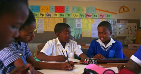 kaapstad : Front view of two young African schoolboys sitting at a desk writing and talking during a lesson in a township elementary school classroom, around them classmates are also sitting at desks writing 4k Stockvideo