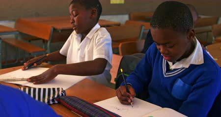 spolužák : Front view close up of two young African schoolboys sitting at their desks writing during a lesson in a township elementary school classroom 4k