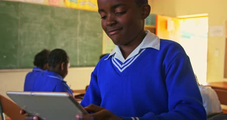 spolužák : Front view close up of a young African schoolboy sitting at his desk looking at a tablet computer and smiling during a lesson in a township elementary school classroom,  in the background classmates are sitting at their desks working 4k