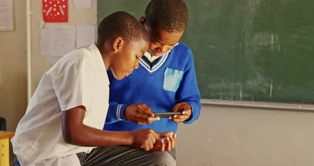socialising : Side view close up of two young African schoolboys looking at a smartphone during a break from lessons in a township elementary school classroom 4k