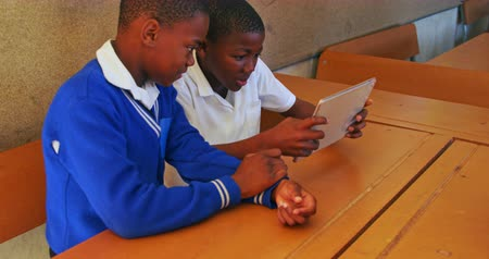 socialising : Side view close up of two young African schoolboys sitting at desks looking at a tablet computer during a break from lessons in a township elementary school classroom 4k