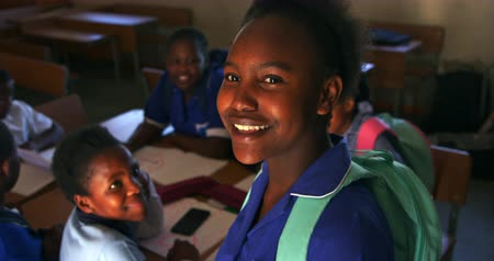 cape town : Portrait close up of a young African schoolgirl wearing her school uniform and schoolbag, turning and looking up to camera smiling, at a township elementary school with classmates sitting at desks in the background 4k
