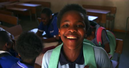 spolužák : Portrait close up of a young African schoolgirl wearing her school uniform and schoolbag, looking up to camera smiling, at a township elementary school with classmates sitting at desks in the background 4k