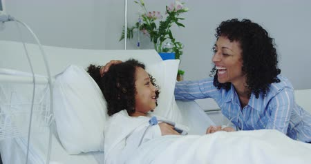 acariciando : Front view of African american mother talking with her son in ward at hospital. They are smiling 4k