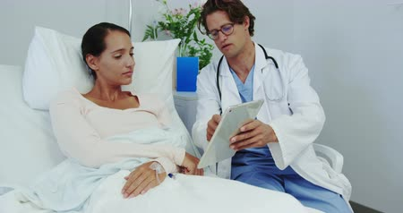 подопечный : Front view of Caucasian male doctor and female patient discussing over digital tablet in the ward. He is showing her medical report 4k
