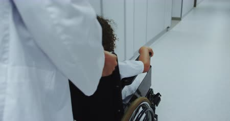 physically : Close-up of Caucasian male doctor pushing pushing African american boy in wheelchair in hospital. They are passing through corridor 4k Stock Footage