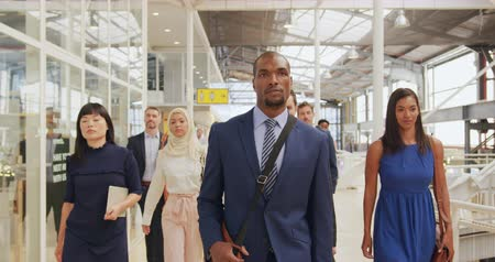 delegate : Front view close up of a diverse group of business delegates walking through a modern foyer to a business conference Stock Footage