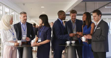socialising : Front view of a diverse group of business delegates talking and drinking coffee during a break at a business conference