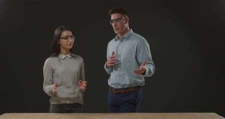 veiligheidsbril : Front view close up of a young Caucasian man and woman wearing protective safety glasses in discussion standing behind a workbench on a black background Stockvideo