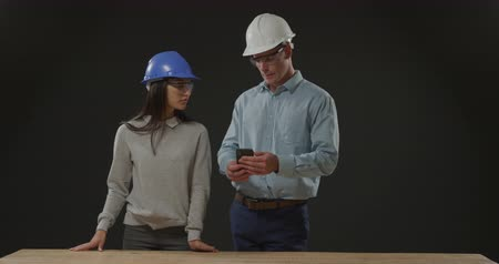 on site research : Front view close up of a young Caucasian man and woman wearing hard hats and protective safety glasses in discussion using a smartphone and standing behind a workbench on a black background