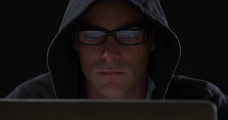 хакер : Front view close up of a young Caucasian man wearing a black hoodie and glasses sitting, looking down and typing on a computer, the reflection of the screen visible in his glasses