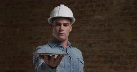 clasificar : Front view close up of a young Caucasian man wearing a white hard hat holding his hand out with a tablet computer resting on it, looking down at it and smiling Archivo de Video