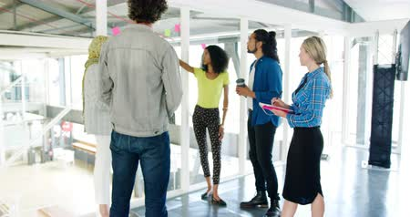 káva : Front view of a young mixed race woman talking to a group of diverse creative professionals standing at a casual meeting looking at coloured notes on a glass wall in a modern office