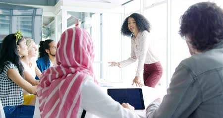 briefing : Side view of a young mixed race woman standing and addressing a group of diverse creative colleagues sitting around a table at a meeting in a modern office Stock Footage