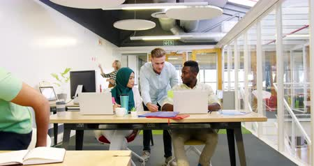 quadris : Front view of a young Caucasian male manager standing, talking and high fiving with a young African American male creative and a young Asian female creative wearing a hijab as they sit working at desks using laptop computers in a busy modern open plan off