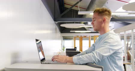 conveniente : Side view close up of a young Caucasian male creative working on a laptop computer at a standing desk and walking on a treadmill in a modern open plan office, with a group of diverse creative colleagues working at desks using computers in the background