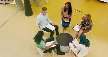 пять : High angle view of a group of diverse creative professionals sitting on chairs holding notebooks and clipboards and talking during a meeting in a modern open plan office