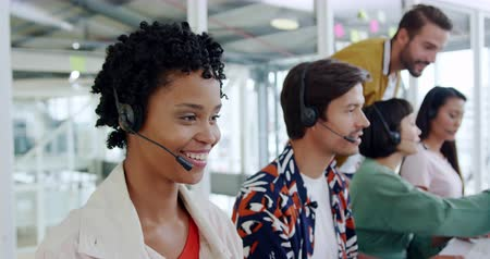 red centre : Side view close up of a group of young multi-ethnic call centre workers wearing headsets and using computers in a modern open plan office, with a young Caucasian male manager talking to them in the background Stock Footage
