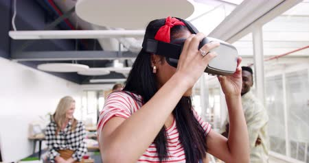 on camera : Front view close up of a young mixed race female creative having fun wearing VR googles and looking around, watched by a diverse group of her colleagues in a modern open plan office