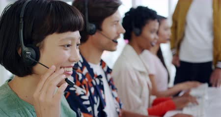 пять : Side view close up of a smiling young Asian female call centre worker typing and talking on a phone headset in a modern open plan office, with a group of young multi-ethnic colleagues wearing headsets and using computers working in the background Стоковые видеозаписи