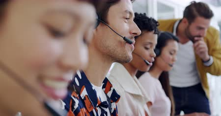 kruk : Side view close up of a group of young multi-ethnic call centre workers wearing headsets and using computers in a modern open plan office, with a young Caucasian male manager overseeing their work in the background