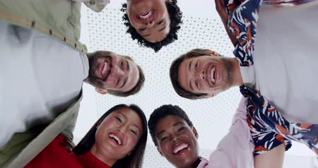 gruppi : Low angle close up of a team of young multi-ethnic creative professionals standing in a circle with their arms around each other looking down to camera smiling in an office