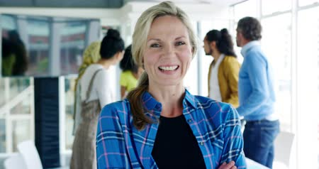 briefing : Portrait close up of a middle aged Caucasian female creative professional looking to camera and smiling in a modern open plan office, with colleagues talking in the background