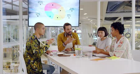 briefing : Front view of a group of young multi-ethnic creative professionals sitting around a table talking at a meeting in a modern open plan office