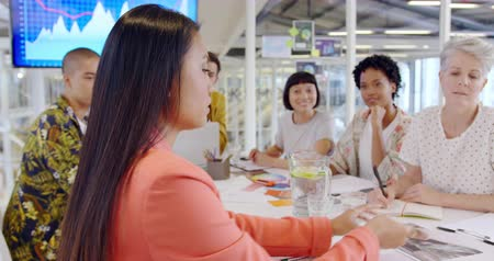brifing : Side view close up of a young Asian female creative talking to a group of diverse creative professionals sitting around a table talking at a meeting in a modern open plan office