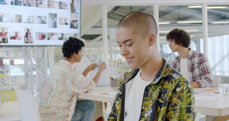 briefing : Side view close up of a young mixed race male creative professional with a shaved head turning and smiling to camera in a modern open plan office, with colleagues talking together in the background