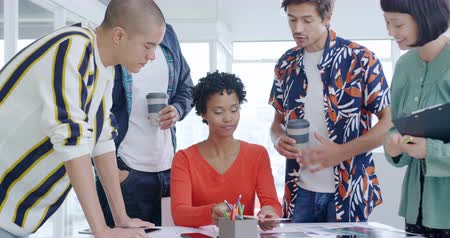 agência : Front view close up of a group of diverse young creative professionals standing around a desk brainstorming at a meeting in a modern office