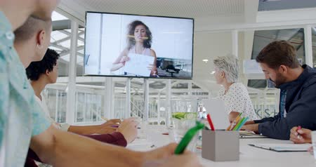 объяснять : Side view close up of a group of diverse creative professionals meeting with a female colleague via a video link in a modern open plan office Стоковые видеозаписи