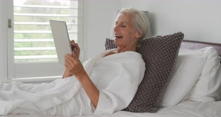 visszavonulás : Side view of a senior Caucasian woman lying on a bed and using a tablet computer