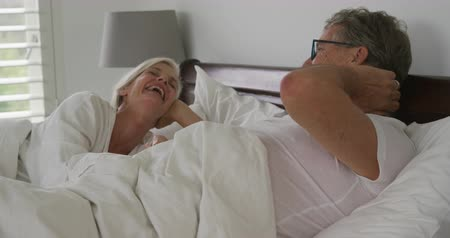 visszavonulás : Side view close up of a senior Caucasian woman and man in bed, talking