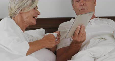 visszavonulás : Front view close up of a senior Caucasian woman and man in bed, holding a coffee cup and using a tablet computer Stock mozgókép