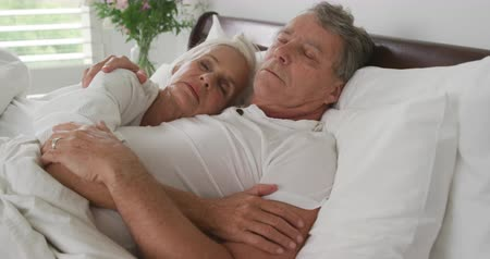 羽毛布団 : Side view close up of a senior Caucasian woman and man in bed, sleeping together