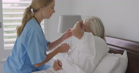 hemşire : Side view of a senior Caucasian woman in bed and a young Caucasian female nurse helping her with a hearing aid