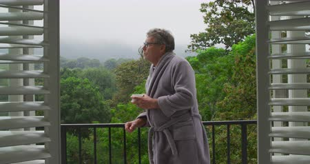 retiro : Front view of a thoughtful senior Caucasian man drinking coffee on a balcony and looking around, with trees behind him Vídeos