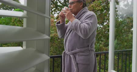 retiro : Side view of a thoughtful senior Caucasian man drinking coffee on a balcony and looking around, with trees behind him