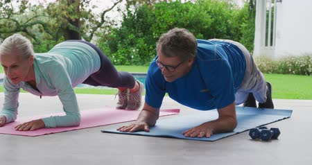 отступление : Front view of a senior Caucasian woman and man exercising in a garden, doing planks Стоковые видеозаписи