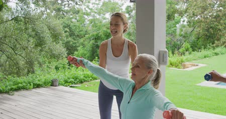 retiro : Front view side up of a senior Caucasian woman exercising with dumbbells in a garden, with a young Caucasian female fitness instructor, with a swimming pool behind her