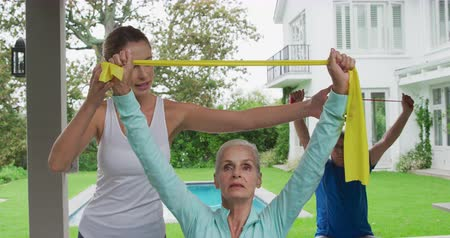 visszavonulás : Front view of a senior Caucasian woman and man exercising with rubber bands in a garden, with a young Caucasian female fitness instructor