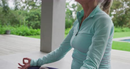отступление : Side view close up of a senior Caucasian woman exercising yoga in a garden Стоковые видеозаписи
