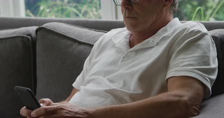 visszavonulás : Side view close up of a senior Caucasian man sitting on a sofa and using a smartphone Stock mozgókép