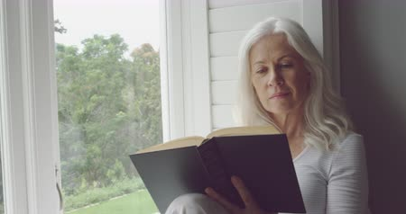 visszavonulás : Side view close up of a thoughtful senior Caucasian woman reading a book and looking out of a window