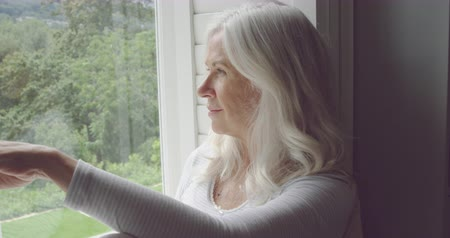 plavé vlasy : Side view close up of a thoughtful senior Caucasian woman sitting and looking out of a window